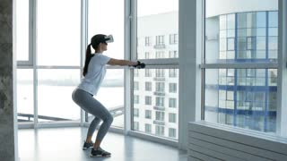 Training process. Full length of young energetic woman wearing virtual reality glasses while doing squats with light weights