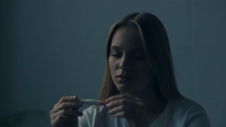 Unplanned child. Close up young stressed woman sitting in the room while holding pregnancy test and feeling frustrated