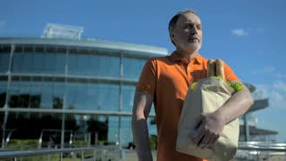 Waist of a serious senior man carrying bag with food