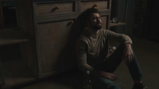 Worn out. Young bearded man feeling tired and inactive while sitting on the floor and drinking alcohol