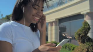 Young lady listening favorite playlist and messaging on phone