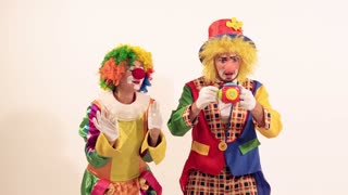 A couple of glad funny clowns playing and singing, when the toy frightens them