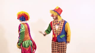 A couple of very funny clowns having fun together trying to inflate a balloon