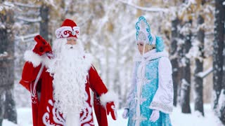 Actors dressed in New Year costumes standing in forest and looking at gifts in bag
