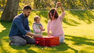 Adorable family opening their little daughter is birthday present together