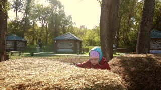 Adorable little girl trying to climb onto the haystack