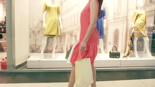 Attractive slender young woman spins round and round enjoying shopping