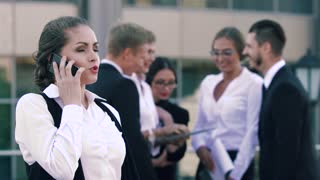 Attractive smart-looking business woman speaking on the phone and her colleagues standing in the background and chatting positively