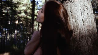 Attractive young woman in the wood standing nude near the tree and playing with her beautiful hair