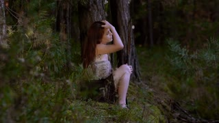 Attractive young woman sitting in the forest alone