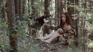 Attractive young woman sitting in the wild with beautiful dog