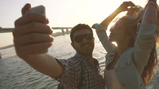 Beautiful couple taking self portrait using smartphone by the river