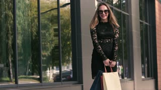 Beautiful fair-hair young woman turns around with shopping bags. Slow motion