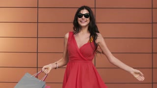 Beautiful girl in red dress turns around with her shopping bags