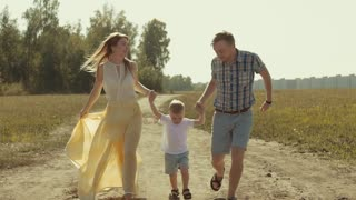 Beautiful mother and handsome father running in the field holding their child is hands and lifting him up