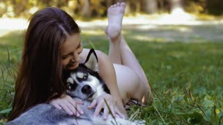 Beautiful nude girl lying in the field and stoking her husky dog