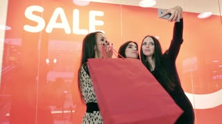Beautiful smiling women taking pictures of themselves standing against red sale sign