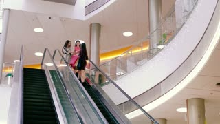 Beautiful young women in shopping mall moving down on escalator to continue their shopping