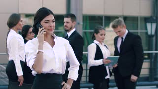 Brunette business woman talking on the phone in front of the camera and in the background her colleagues are standing