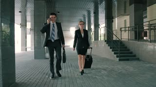 Business man talking on the phone and business woman walking with him pulling her suitcase