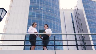Business people standing on terrace of office building in the center of city and doing their business