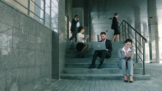 Business people working outdoors sitting on the stairs on a summer day