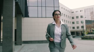 business woman running late for work and looking at the time