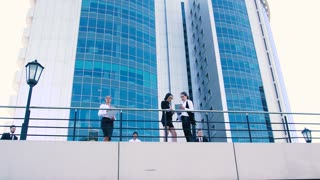 Business women and business men talking on terrace. From below shot