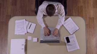 Businessman is working hard in his office and stops to answer the phone call