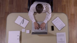 Businessman working on lap-top computer and answering the phone-call