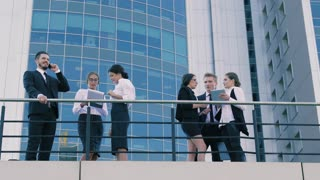 Busy business people outdoors on the terrace of an office building