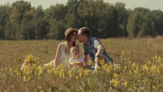 Cheerful family having fun outdoors in summer field
