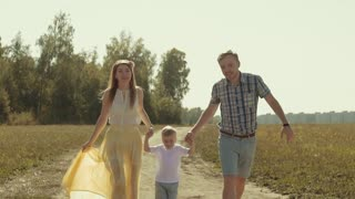 Cheerful family running on countryside road holding their son is hands lift him up to the air