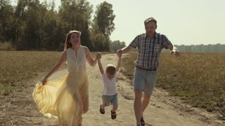 Cheerful Parents lift their child up, while he comes through the air waddling his legs
