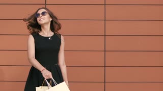 Cheerful shopping woman in black dress with shopping bags