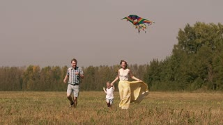 Cheerful young family running in grass. Little kid flying a kite