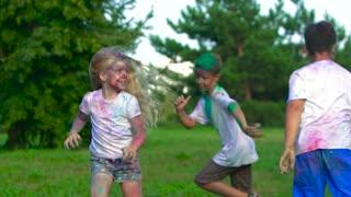 Children smeared in holy powder running around to catch each other