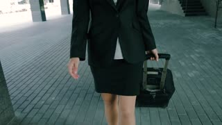 Close-up of an attractive blond businesswoman walking with travel luggage to an office building