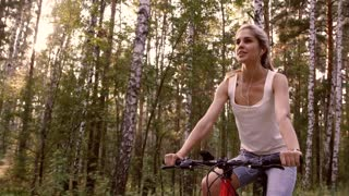 Close-up of blond girl riding her bicycle in the forest