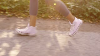 Close-up of female legs running gently on paved road