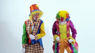 Close-up of jumping clowns dressed in colorful and funny costumes