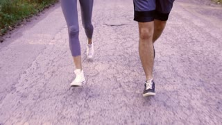 Close-up of running couple on a paved road