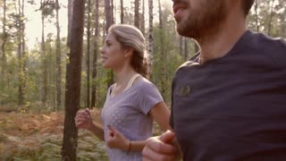 Close-up of young couple jogging together in the forest