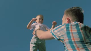 Close-up of young fair-skinned father throwing his son in the air