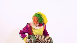 Comic young clown playing with harmonica pretending she can play it