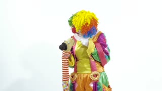 Coming circus clown playing with puppet amusingly