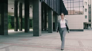 Confident young business woman is sent to the office building documents