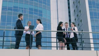 Coworkers standing outdoors and having hot discussion on a busy working day