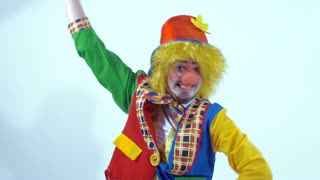 Dancing and smiling circus clown turning around and waving an orange cloth