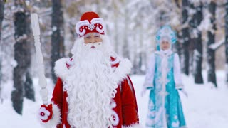 Ded Moroz Father Frost and Snegurochka Snow Maiden walking in the forest and having fun at the new year Eve